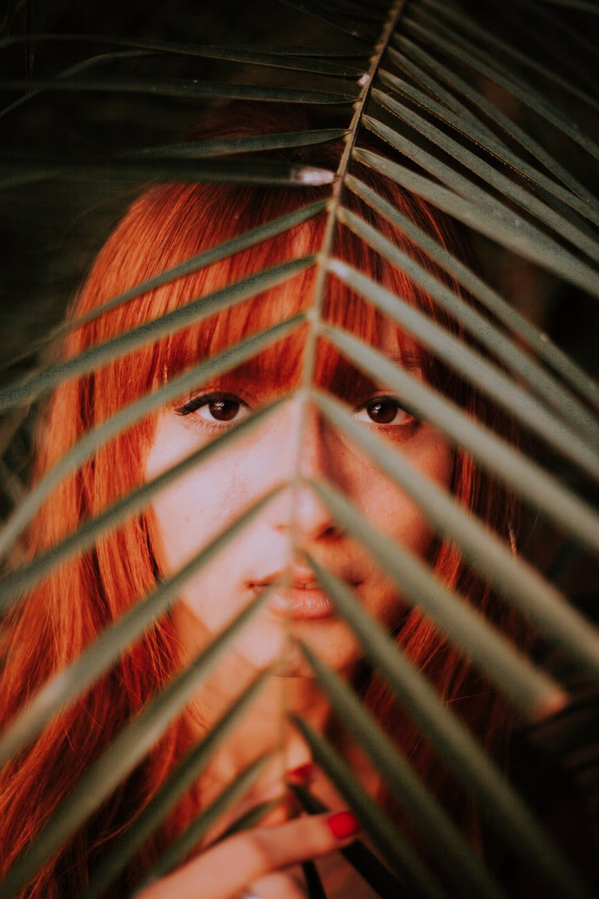 red haired woman covered by green leaf